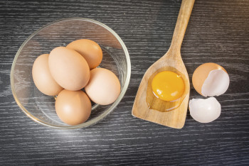 Group of brown eggs and yolk in wooden spoon on wooden backgroun